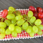 33212487 - nice fresh grapes decorated on a wooden plate and doily