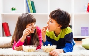37673747 - little girl and little boy enjoy eating popcorn at home.