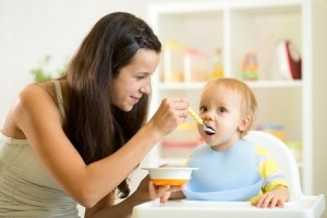 33616562 - mother spoon-feeding her child boy at kitchen